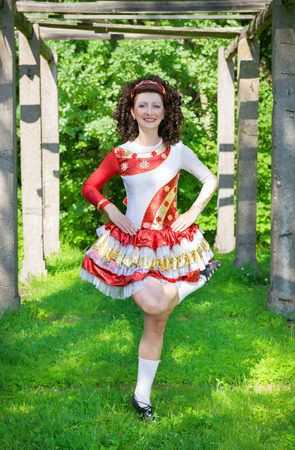 Young woman in irish dance dress and wig dancing outdoor photo