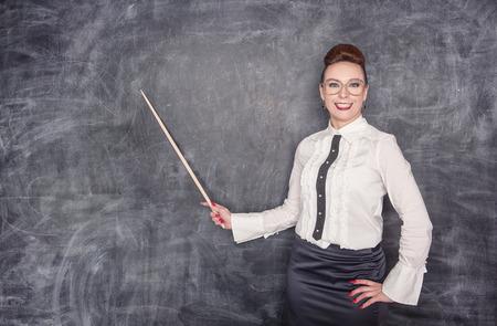 Smiling teacher with pointer on the school blackboard background Zdjęcie Seryjne