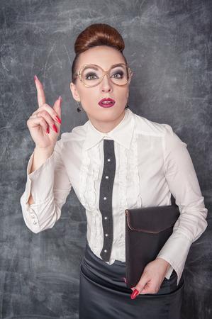 stringent: Strict teacher in eyeglasses with folder showing finger  Stock Photo
