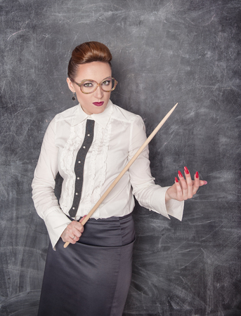 blouse sexy: Strict teacher with wooden pointer looking at someone