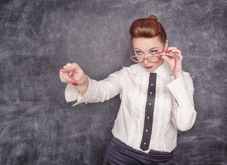Strict teacher in eyeglasses showing on someone by her finger  photo