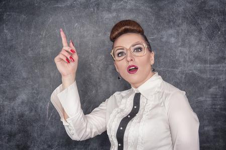 stringent: Strict teacher in eyeglasses showing finger on the school blackboard