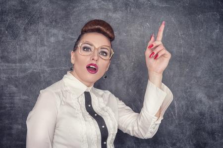 parody: Strict teacher in eyeglasses showing finger on the school blackboard