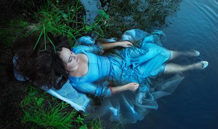 mojado: Hermosa mujer ahogada joven en vestido azul tendido en el agua