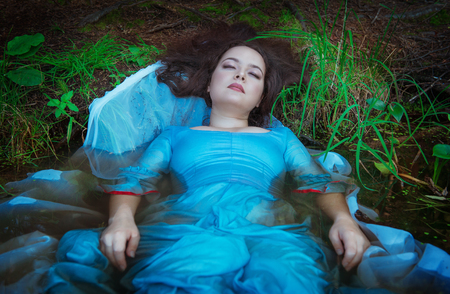 Young beautiful drowned woman in blue dress lying in the water photo