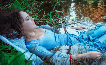 murdering: Young beautiful drowned woman in blue dress lying in the water