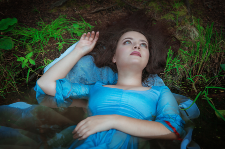 murder scene: Young beautiful drowned woman in blue dress lying in the water