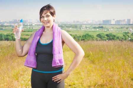mujeres gordas: Fitness mujer de talla grande con una toalla y botella de agua al aire libre