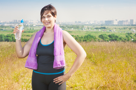 fat: Fitness plus size woman with towel and water bottle outdoor