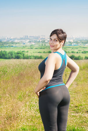 Smiling fitness plus size woman standing outdoor Stock Photo