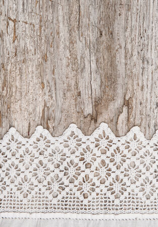 Lace fabric on the old wooden background