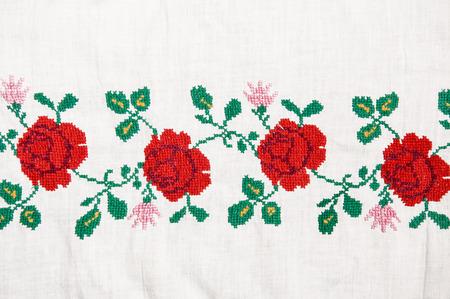 punto cruz: Flores de color rojo bordado en el lino textil Foto de archivo