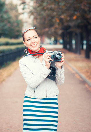 Beautiful young woman with old retro camera outdoor photo