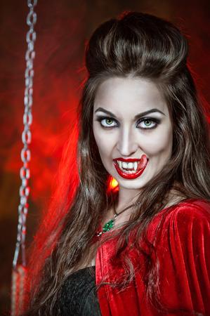 Beautiful halloween vampire woman with long tongue photo