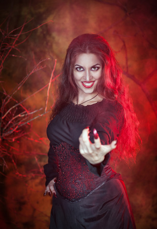 Beautiful woman with long hair in halloween style beckoning finger photo