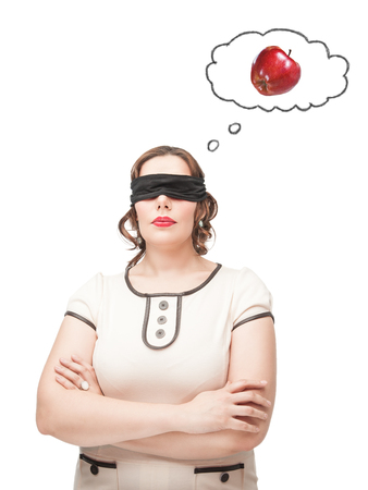 Blindfold beautiful brunette plus size woman dreaming about apple isolated photo