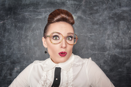 Surprised teacher with eyeglasses on the school blackboard background photo
