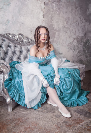 Beautiful woman in blue medieval dress putting stockings on the sofa