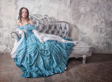 Beautiful young woman in blue medieval dress on the sofa photo