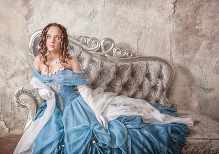 ruche: Beautiful young woman in blue medieval dress on the sofa