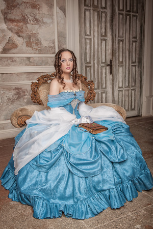Beautiful young woman in blue medieval dress on the armchair photo