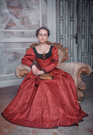 ruche: Beautiful young woman in red medieval dress on the armchair Stock Photo