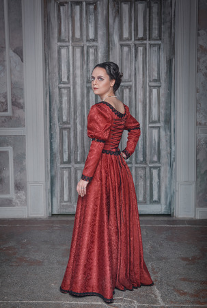 era: Beautiful young woman in red long medieval dress