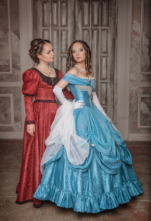 Two beautiful young women in blue and red medieval dresses  photo