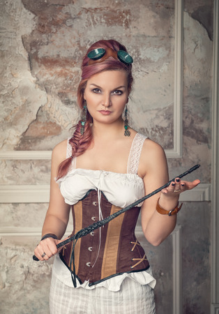 Beautiful steampunk woman with pink hair holding whip Stock Photo