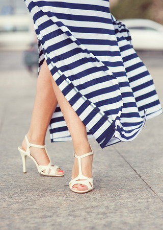 Legs of woman dressed long striped dress  photo