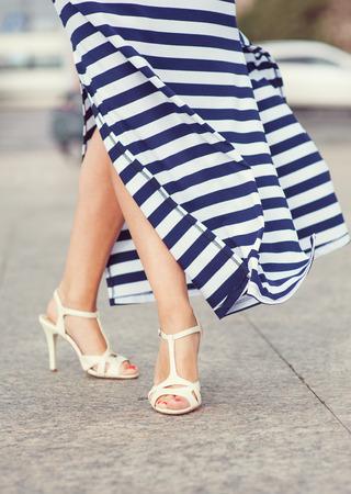 Legs of woman dressed long striped dress  photo