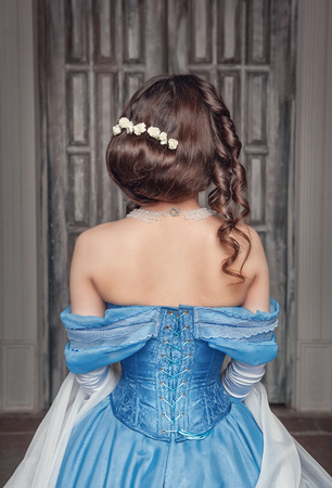 Portrait of young beautiful medieval woman in blue dress, back  photo