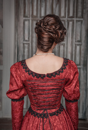 Portrait of young beautiful medieval woman in red dress, back  Stock Photo