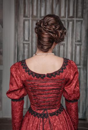 Portret van jonge mooie middeleeuwse vrouw in rode jurk, terug