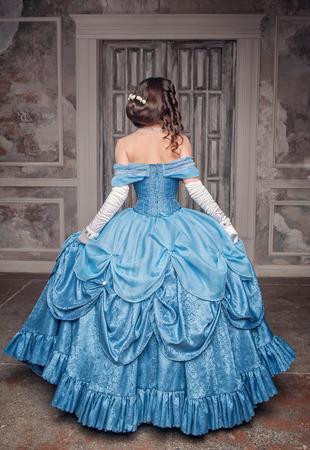 Prachtige middeleeuwse vrouw in lange blauwe jurk, terug