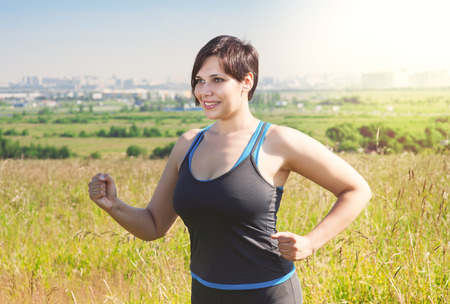 Smiling fitness plus size woman running outdoor