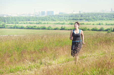size: Smiling fitness plus size woman running outdoor