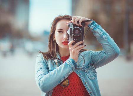 Jonge mooie hipster meisje met retro camera in de stad Stockfoto