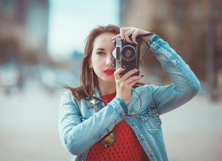 photographers: Young beautiful hipster girl with retro camera in the city