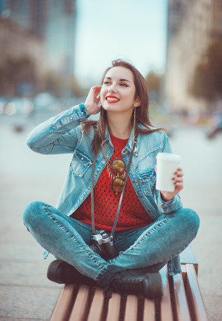 Young beautiful hipster girl drinking coffee in the city photo