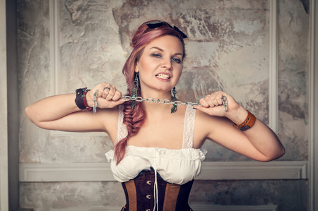 Beautiful steampunk woman dressed corset with metal chain photo