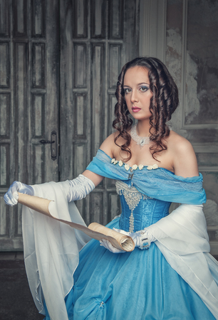 Beautiful young woman in blue medieval dress with scroll letter in the room photo