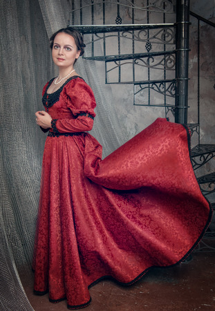 ruche: Beautiful young woman in red fluttering medieval dress Stock Photo