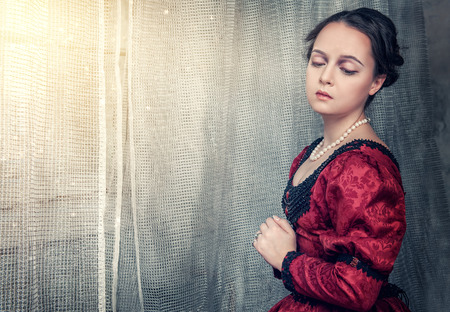 Sad beautiful young woman in red medieval dress near window photo