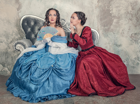 Two beautiful young women in blue and red medieval dresses gossip on the sofa