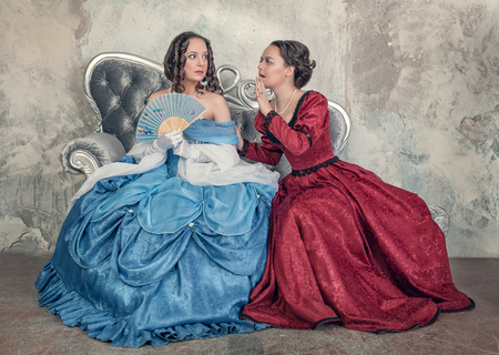ruche: Two beautiful young women in blue and red medieval dresses gossip on the sofa