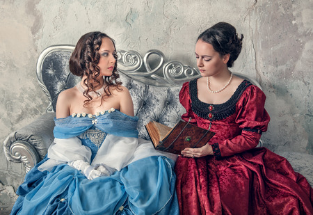 Two beautiful young women in blue and red medieval dresses on the sofa reading book photo