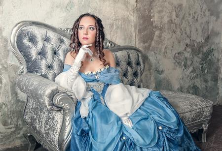 abito medievale: Bella giovane donna in blu vestito medioevale sul divano Archivio Fotografico