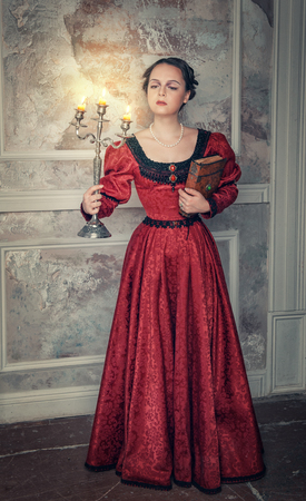Beautiful young  woman in long red medieval dress with candelabrum and book photo