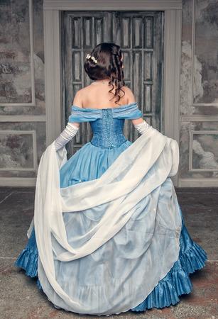 Beautiful medieval woman in long blue dress, back